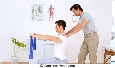 Physiotherapist checking shoulders of patient pulling...