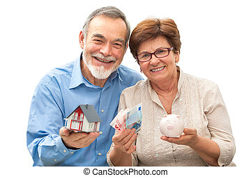 senior couple holding a house model and piggy bank -...