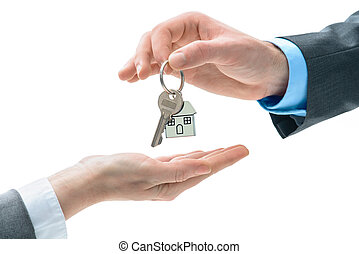 Man is handing a house key to other hands. Concept of real...