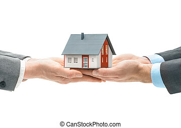 Hands giving house model to other hands. Concept of real...