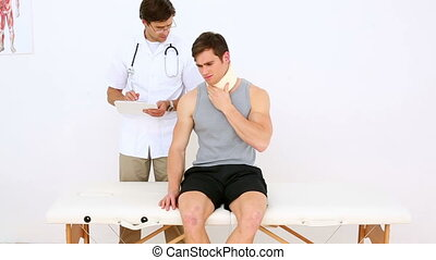 Physiotherapist talking to patient wearing a neck brace in...