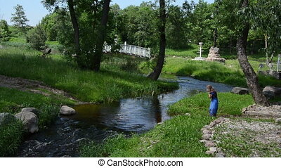 girl wade through stream - girl comes torrential river takes...