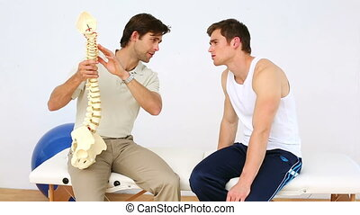 Physiotherapist speaking to patient showing him a spine...