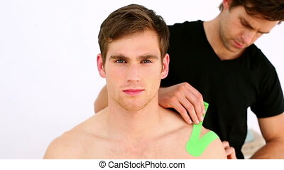 Physiotherapist applying green tape - Physiotherapist...