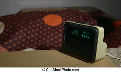 Woman waking up and stopping alarm clock lying in bed at...