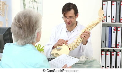 Chiropractor showing spine model to his patient in an office...