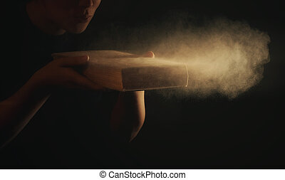 Blowing dust off old book - A woman blowing the dust off of...