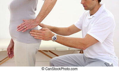 Physiotherapist touching senior patients hips at the...