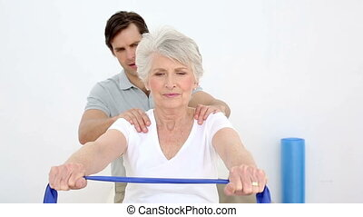 Physiotherapist checking senior patients shoulder alignment...
