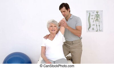 Physiotherapist checking senior patients shoulders at the...