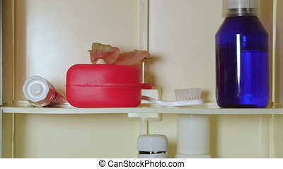 Man takes out dentures from medicine cabinet
