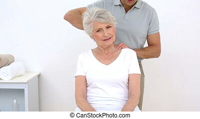 Physiotherapist stretching his senior patient