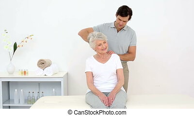 Physiotherapist smiling at camera with senior patient at the...