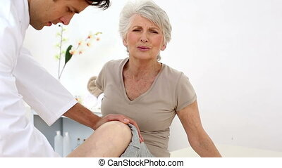 Injured patient wincing while doctor checks knee - Injured...