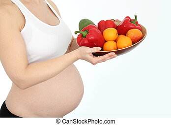 Pregnant woman with fruit and vegetables bowl