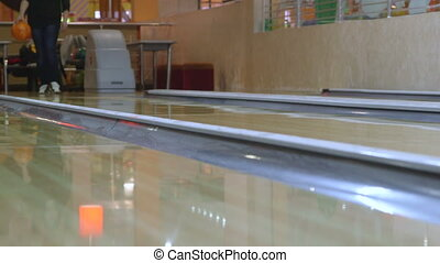 Player throws a bowling ball down the alley