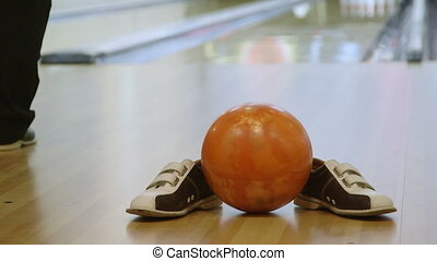Bowling alley with shoes and ball, in the background person...