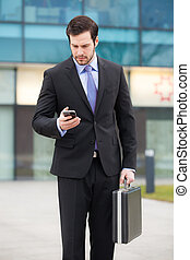 businessman looking at his phone in front of an office...