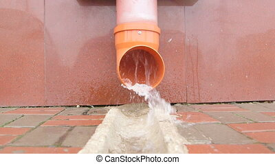 Rain water flowing from drain pipe closeup