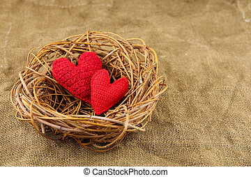 Two handmade hearts in the nest - Two red handmade hearts in...