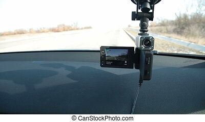 Parked car with recording DVR on windshield