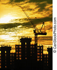 silhouette of crane and building construction and sun set...