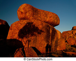 Devils Marbles in Australia, huge round red rocks, sunset
