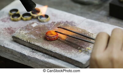 Jewelery making - Close up of Jeweler crafting golden rings...