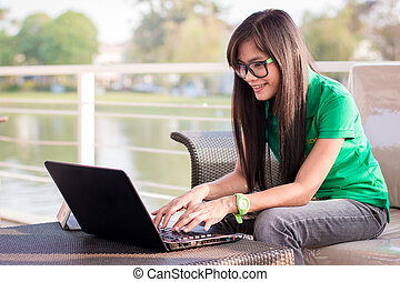 Pretty Asian female adolescents use technology for...