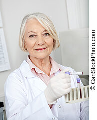 Scientist Analyzing Blood Sample In Laboratory - Portrait of...