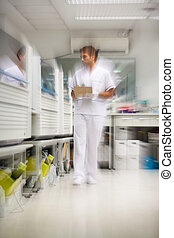 Technician Walking In Storage Room - Blurred motion of male...