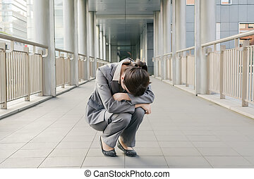 Business woman feel helpless and sadness and squat on ground...