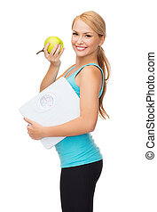 sporty woman with scale and green apple - diet, sport and...