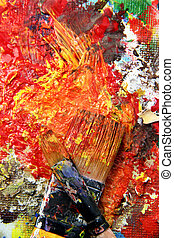 Beautiful vivid art palette and mix of paintbrushes in fresh...