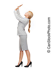 businesswoman pushing up something imaginary - business and...
