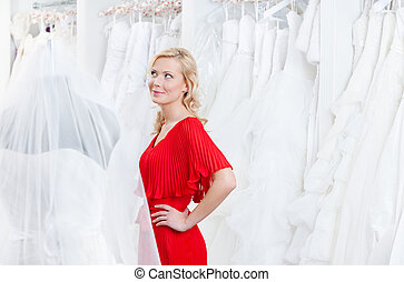 Looking for wedding gown - Pretty girl examines wedding...