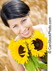 Close up of lady with sunflowers in the field - Close up of...