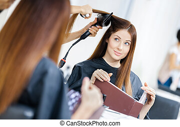 Reflection of beautician doing haircut for woman -...
