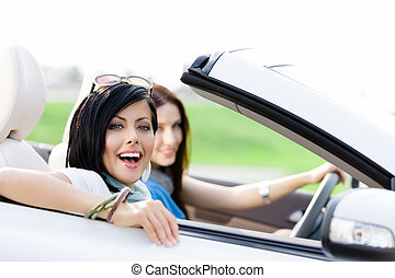 Two happy friends drive the cabriolet - Two happy friends in...