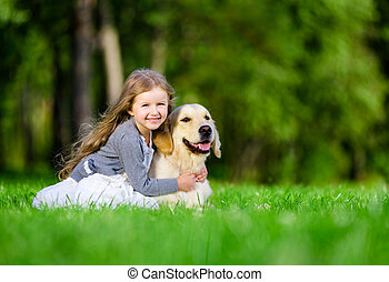 Little girl sitting on the grass with golden retriever in...