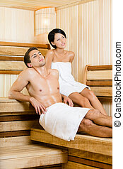 Half-naked man and young woman relaxing in sauna Concept of...