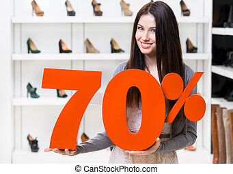 Woman keeps the model of 70 sale on shoes standing at the...