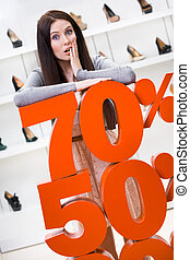 Woman showing the percentage of sales on footwear in the...