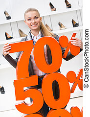 Woman showing the percentage of sales on high heeled shoes...