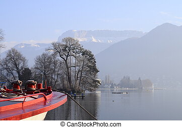 Annecy lake and city  with red front of a ferry boat