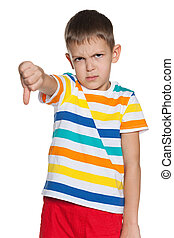Upset boy holds his thumb down - An upset boy holds his...