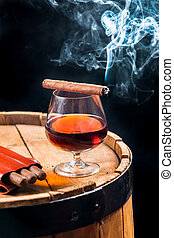 Aroma of Cuban cigars and cognac on black background