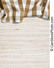 folded tablecloth over bleached wooden table