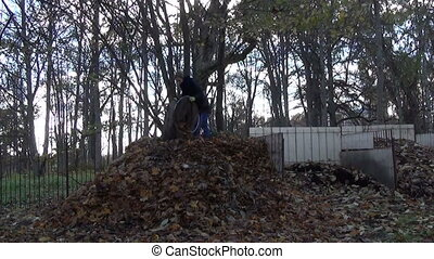 gardener girl compost - worker shake lot of dry leaves on...