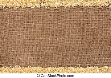 Millet  lying on sackcloth with space for text